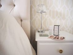 Image of ARK Skincare Age Defend Night Regenerating Treatment Cream on a white bedside cabinet with gold drawer pulls next to a cream upholstered button back bed