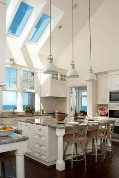 What a beautiful and large white kitchen with white cabinets, dark wood floors, vaulted ceilings with skylights, granite countertops, large kitchen island. More via http://forcreativejuice.com/elegant-white-kitchen-interior-designs/