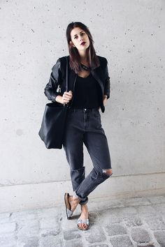 Elisa from www.schwarzersamt.com is wearing a mom jeans from urban outfitters, a black top from H&M, a leather jacket from H&M, a one shoulder bag from Mango and silver Birkenstocks. The denim look is one of the outfits for the MBFW SS15.