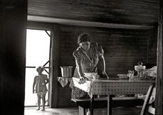 """""""Knee Baby""""-July 1939, Person County, North Carolina. Wife and child of tobacco sharecropper. The littlest girl comes in from outside for something to eat while Mother is doing her housework. """"Knee Baby"""" comes from the common occurrence that when the (infant) baby was being fed the older toddler would hang onto Mother's knee. This was usually in a bid for the attention lost when the infant kicked the toddler out of the 'baby' position and, in poor families, often actually away from the…"""