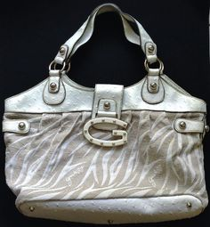 """EXTERIOR: QUILTED WHITE ZEBRA-PRINT ON DARK BEIGE JACQUARD     WHITE PATENT """"DOT"""" EMBOSSED LEATHER-LIKE    trim POLISHED SILVER-TONE hardware    FULL ZIPPER CLOSURE  SILVER-TONE """"GUESS"""" LOGO PLATE    MEASUREMENTS are approximate and are of the exterior of bag   (W=width; H=height; D=depth):    Dimensions:  12"""" (at bottom) - 16.5"""" (at top)DUAL Straps drop:  8.5""""  (22cm)   - this is the distance from the top of the straps to the the top of the bag    INTERIOR: satin interior1 zipper in centre1…"""