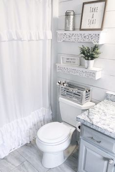Shabby chic combines something old with something new. The rustic shelves and ruffled shower curtain are definitive of this style.It's contrasted with the modern granite counter tops and stone tile floor.