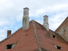 """Some old style chimneys and some """"eye-like"""" attic windows on the roofs of an old house in downtown (medieval area) Sibiu, Transylvania, Romania."""