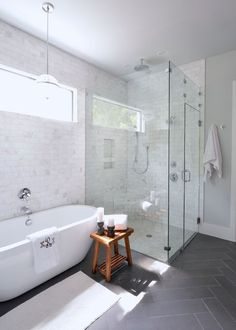 White bathroom, free standing tub, monogrammed towel, grey floor tile, glass shower, pendant lighting above tub | Lilli Design: