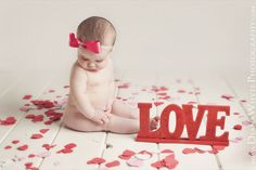 plank flooring, white backdrop, flower petals or paper hearts and a cute little naked baby