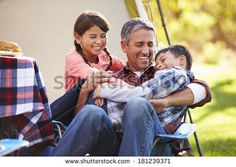 Father With Children Enjoying Camping Holiday In Countryside