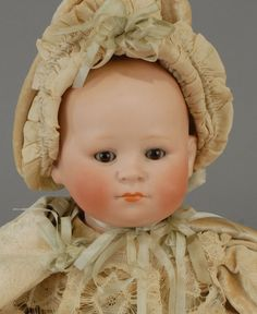 Heubach Köppelsdorf character Baby marked 339*5/0 featuring a perfect bisque solid-dome head with exquisite coloring and painting, unusual brown glass sleep-eyes, and a closed mouth. On a cotton-stuffed cloth body that is fitted with celluloid hands, baby wears a fabulous cream silk velvet gown that is decorated with lace and ice blue ribbons, plus a fantastic lined cape, and a matching baby cap.