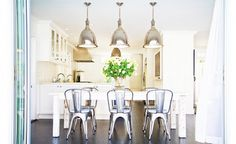 White cupboards, silver hanging lights, steel chairs, white rectangular dining table