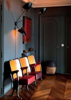 <p>D'anciens fauteuils de salle de spectacle sont adossés au mur gris anthracite. <br />Applique Serge Mouille.<br />Posé sur le parqué d'origine en chêne à chevrons,...