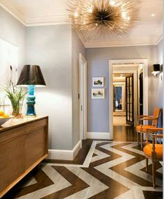 Chic, eclectic foyer with sea urchin pendant chandelier, coffee stained wood floors with painted silver chevron herringbone pattern, orange Louis chairs, mid-century modern credenza, turquoise blue lamp and gray walls paint color.