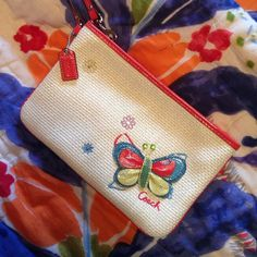Rare Coach Butterfly Large Wristlet✨Reduced✨ Rare authentic coach straw butterfly and flowers large sized Wristlet. Used only a couple times while in Hawaii on vacation. Perfect condition. Leather butterfly detailing. Orange leather trim and hang tag. Coach Bags Clutches & Wristlets