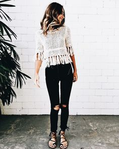 don't love the knee rips in her jeans but do love the sweater and the tassels