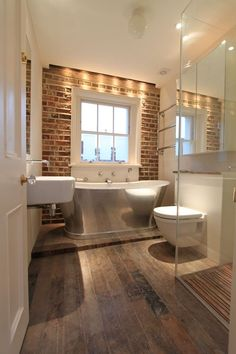 Don't love the stainless tub but love the worn wood floors and brick!