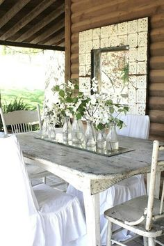 Porch shabby white ...it's the details...jars with flowers, tin tiles around window, chippy table, white chair covers