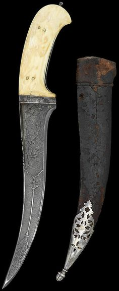 Indian pesh kabz (curved dagger), 18th century, sharply pointed double-edged watered steel blade, with thickened flat spine, the forte with swirling foliate motif enclosed by lobed design terminating in flower, the tip of blade with engraved swirling design, the centre of the hilt with parrots amidst a scrolling floral vine, the leather-clad wood scabbard openwork silver finial 31.7 cm. long.