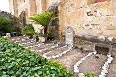 cemetery of Carmel Mission with graves of indians decorated with shells California Missions, Cemetery, Stepping Stones, Spanish, Shells, Outdoor Decor, Conch Shells, Stair Risers, Seashells