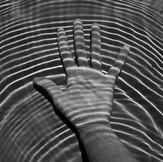 Shadows and light play in ripples in water, hand. Filatures Maupetit