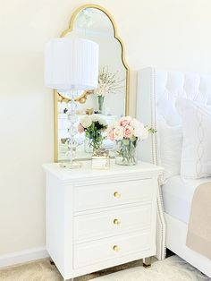 Love this pretty white nightstand in this pretty master bedroom. Copy this look with a few key decor pieces like a good mirror, pretty white dresser, gold knobs and fresh flowers! #masterdecor #glambedroom #masterbedroomideas #goldaccents #goldbedroomaccents #modernbedroomdecor