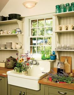 I love the simple charm of this cottage kitchen! The bead board and butcher block counter top is my favorite. Just swap some of the open shelves for cabinets and I would change the lower cabinet's green color to blue probably. :).