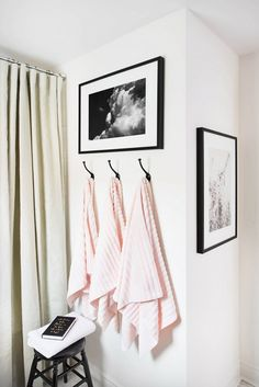 Black and white bathroom with hanging pink towels, black and white art, and white shower