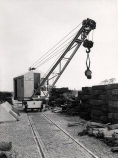 Nederland, vòòr 1940. Hijskraan op rails, bielzen. [De spoorrailkraan is in 1939 geleverd aan de walserijen van Van Leer op het Hoogovens terrein in Velsen. De kraan is in de weer met zogenaamde broodjes gietijzer. Die werden door Hoogovens geleverd en werden bij Van Leer uitgewalst.]