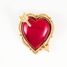 Vintage bright red cabochon heart. Cupids arrow pierces the heart in gold. The brooch is gold plated and is textured. The cabochon is has no backing and light gleams through. The brooch is in good vintage condition and has minor wear to the cabochon and gold plate. The item is signed ART. The company was Mode Art created by Arthur Pepper. Mode Art was formed in the late 1940s and lasted until the 1970s. There is not much known about Art other than the jewelry was high quality and looks like…