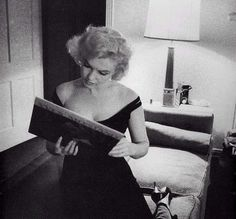 """Marilyn Monroe looking at an album by Yves Montand at a dinner in his suite during the filming of """"Let's Make Love"""" by Bruce Davidson, 1960"""
