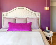 A bed with padded headboard is placed against the accent wall of this purple bedroom. Colorful throw pillows fit the color scheme, and a pendant light provides illumination for bedtime reading.