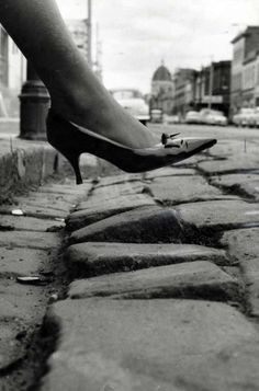 A hazard for high heels - Women stepping off the footpath in Gertrude St. have a rough path ahead, 1964