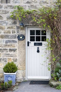 Photo about Old stone cottage with white stable door and small window to the side, two small conifers in terracotta pots either side of the door. Image of cottage, terracotta, building - 23624062 Cottage Front Doors, Cottage Windows, Front Door Porch, House Doors, House Front, Cottage Style Doors, Cottage Front Garden, Country Front Door, Door Entryway