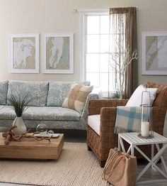 Casual, shore-inspired furniture with wood and woven finishes act as neutrals in the room. Sandy beige and watery blues mixed with beachy textures mimic a relaxing seascape. (Nice low table and unusual window treatment.)