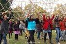 Multiculturele vrouwengroep bouwt samen een bamboe piramide met tekstberichten.