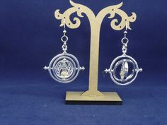 A touch of time, silver toned Harry Potter Time Turner earrings. Earrings are 2.5in silver metal time turner with tan/gold sand on silver metal chain and silver metal earring hooks. Each piece of jewelry comes in a protective white box for its care.  *Please note that buyers are responsible for any and all duties and customs charges that may be incurred.  ♥ Want to save for later? Click on the heart at right that says Add item to favorites. ♥ Ready to buy? Click the big green Add to cart…
