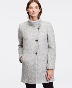 """Layer on the luxe this winter with our funnel neck topper - a marvel of haute hues and sophisticated textures. Funnel stand collar with hidden snap closure. Long sleeves. Button front. Vertical on-seam welt pockets. Lined. 32 1/2"""" long."""