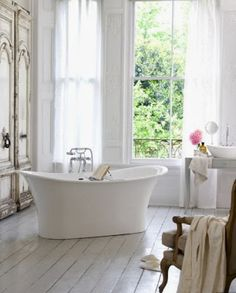 clean, white bathroom with a freestanding tub, white linens, an open window, and fresh flowers -- 6 Beautiful & Luxurious Bathrooms from Pinterest from Bathroom Bliss by Rotator Rod