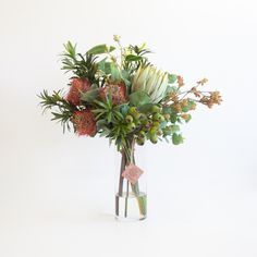 Beautiful, life-like rusty orange leucospermums, green protea and kangaroo paw with a lovely mix of foliage and gumnuts.