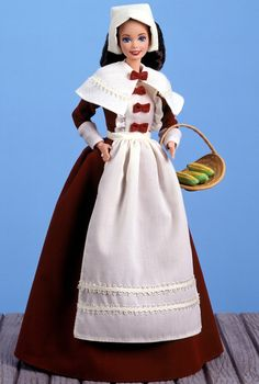 Pilgrim Barbie® doll is dressed for Thanksgiving in a maroon dress with ivory collar, apron, and bonnet. She carries a basket of corn, and comes with a storybook detailing her Mayflower voyage to America,