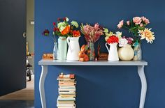 View of hallway table with display of artificial flowers in vases and jugs. Stack of vintage books underneath.