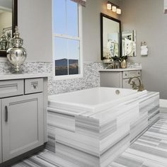 Soak in this gorgeous tiled bathroom in grey and white by Richmond American Homes. #bathrooms