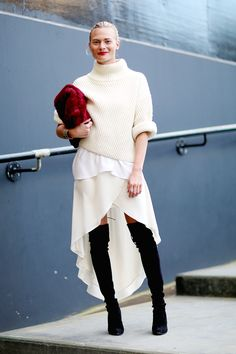 Street style: off white turtleneck sweater, blouse, chiffon asymmetrical skirt, black suede over knee boots, burgundy fur clutch