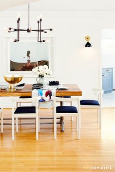 A dinning space with a reclaimed wood table, mod chairs,  and an exposed bulb chandelier