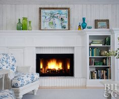 Using fireplace brick paint to turn the facade white started the process of bringing this fireplace back to life. A wood surround enhances the look. Classic-lined built-ins integrate the fireplace, bookshelves, and an entertainment unit. The surround, built-ins, and walls were also painted white to brighten the room and layer on the cottage charm. Cottage Fireplace, Paint Fireplace, Brick Fireplace Makeover, Fireplace Built Ins, Fireplace Remodel, Fireplace Surrounds, Fireplace Design, Fireplace Ideas, Fireplace Brick