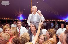Great moment of the father of the groom being carried on his son's shoulders during a dance at the tented reception in Stowe, VT.  This is why we love documentary wedding photography!