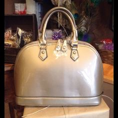 Taupe Patent Satchel This faux patent bag features top double zipper closure, short handles, detachable shoulder strap, metal feet at the bottom for protection, inside zipper pockets and two slip pockets, one exterior zipper pocket. Fully lined. (This closet does not trade or use PayPal) Bags Satchels