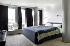 Soverommet er minimalistisk innredet. To store søyler på hver side av sengen er malt i grått og rammer inn sengen. Vinduene dekker en hel vegg, fra tak til gulv, og er dekket av tunge mørke gardiner. Styling: Tone Kroken.