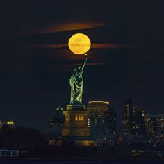 The statue of liberty stands on a tall pedestal holding a torch up high with buildings of New York City in the background and a huge full moon shining above it.