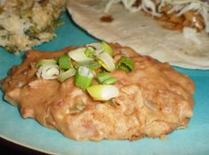 Refried Beans. (Suggestion: Make beans from scratch. Saute the onions and add some garlic. Brown the butter. Garnish with chopped green onions. If using canned beans that are salted, skip the recipe salt. It would be better to mash the beans in a food processor. Taste before adding the cheese in order to decide if the cheese should be stirred in or melted on top.)