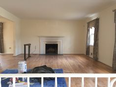 Living Room Before, yellow walls were prepared for new paint and dated window treatments and a fireplace screen were removed