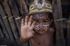 A decorated child from the Dani tribe watches the festivities from a traditional wooden hu...