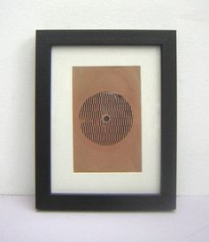 This is a framed pictured vinyl record. During the communist era in  Eastern Europe you could purchase stories or have personal messages  recorded onto special thin plastic vinyl which could be played on a  record player. The pieces were always cut either square or rectangle  though the grooves for the record are the same as on a normal record This may be a personal message or just a recording of a poem This record is mounted 18.5cm x 23.5cm